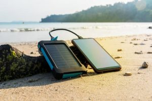 Portable solar panel on the beach with smartphone