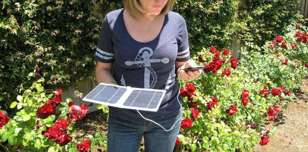 Woman holding Solar panel charger for phone