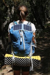 Woman hiking with Solar Charger hooked on Backpack