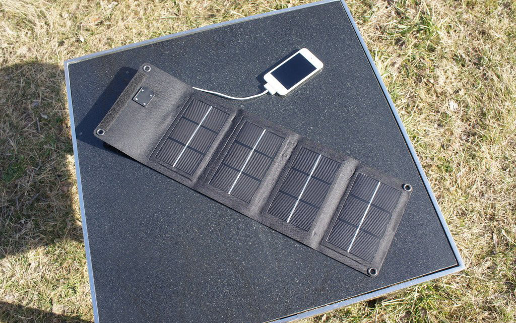 Multiple Panel foldable solar charger on table charging phone