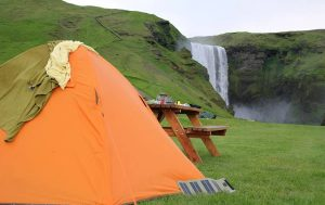 Tent with a solar charger on the side facing waterfall