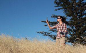 woman charging phone in the outdoors using solar charger